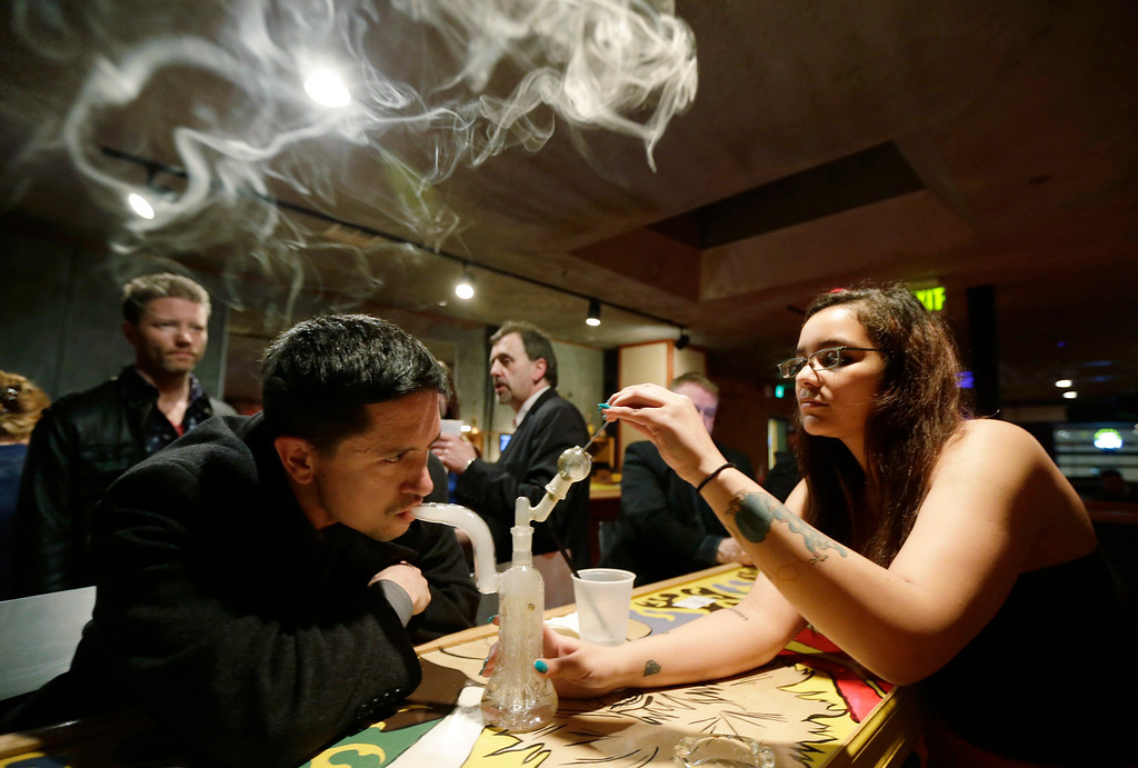 Description of . John Connelly, left, inhales marijuana vapor just after midnight Saturday, March 2, 2013, with the help of bar worker Jenae DeCampo, right, in the upstairs lounge area of Stonegate, a pizza-and-rum bar in Tacoma, Wash. Owner Jeff Call charges patrons a small fee to become a member of the private second-floor club, which prohibits smoking marijuana, but does permit