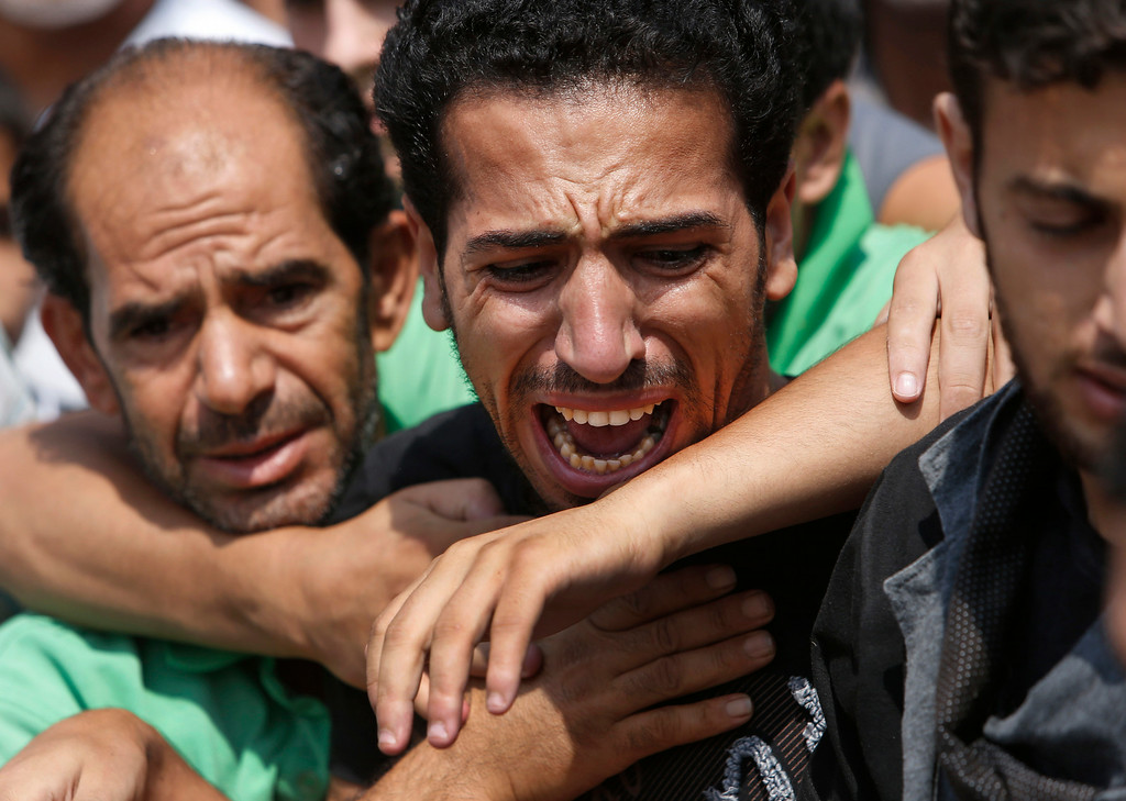 Description of . A relative bursts into tears as mourners try to comfort him as they gather around the bodies of seven members of the Kelani family, killed overnight by an Israeli strike in Gaza City, during their funeral in Beit Lahiya, northern Gaza Strip, on Tuesday, July 22, 2014. Ibrahim Kelani, 53, his wife Taghreed and their five children, were killed in the strike on a Gaza City high rise. Ibrahim's brother Saleh Kelani said Tuesday that his brother and his brotherís children, ranging in age from four to 12, had German citizenship, while his wife had not. The family had rented the apartment in the high-rise after fleeing their home in the northern Gaza town of Beit Lahiya which came under heavy shelling by the Israeli army. (AP Photo/Lefteris Pitarakis)
