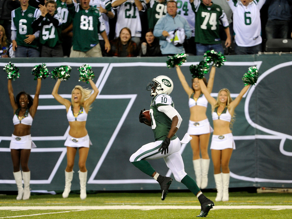 Description of . New York Jets wide receiver Santonio Holmes (10) runs for a touchdown after catching a pass from Geno Smith during the second half of an NFL football game against the Buffalo Bills Sunday, Sept. 22, 2013, in East Rutherford, N.J. (AP Photo/Bill Kostroun)