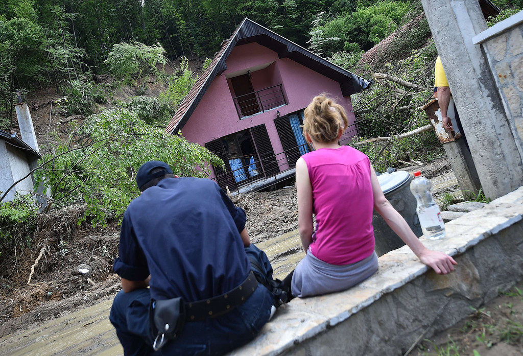 Description of . A couple looks at their house damaged by flooding and landslides in Krupanj, some 130 kilometers south west of Belgrade, on May 20, 2014, after the western Serbian town was hit with floods and landslides, cutting it off for four days. Serbia declared three days of national mourning on May 20 as the death toll from the worst flood to hit the Balkans in living memory rose and health officials warned of a possible epidemic.    AFP PHOTO / ANDREJ  ISAKOVIC/AFP/Getty Images