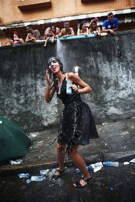 Description of . A reveler dances during the \'Ceu na Terra\' street carnival bloco on March 1, 2014 in Rio de Janeiro, Brazil. Carnival is the grandest holiday in Brazil, annually drawing millions in raucous celebrations.  (Photo by Mario Tama/Getty Images)