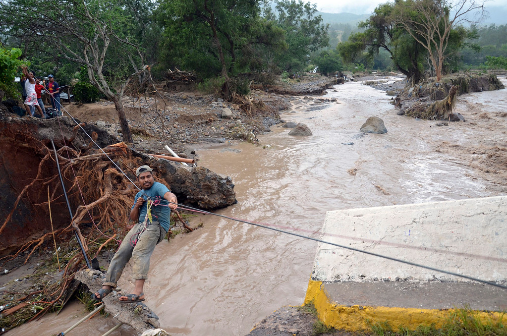 Description of . A man uses a makeshift zip line to cross a river after a bridge collapsed under the force of the rains caused by Tropical Storm Manuel near the town of Petaquillas, Mexico, Wednesday, Sept. 18, 2013. The death toll from devastating twin storms climbed to 80 on Wednesday as isolated areas reported to the outside world. Mexican officials said that a massive landslide in the mountains north of Acapulco could drive the number of confirmed dead even higher. (AP Photo/Alejandrino Gonzalez)