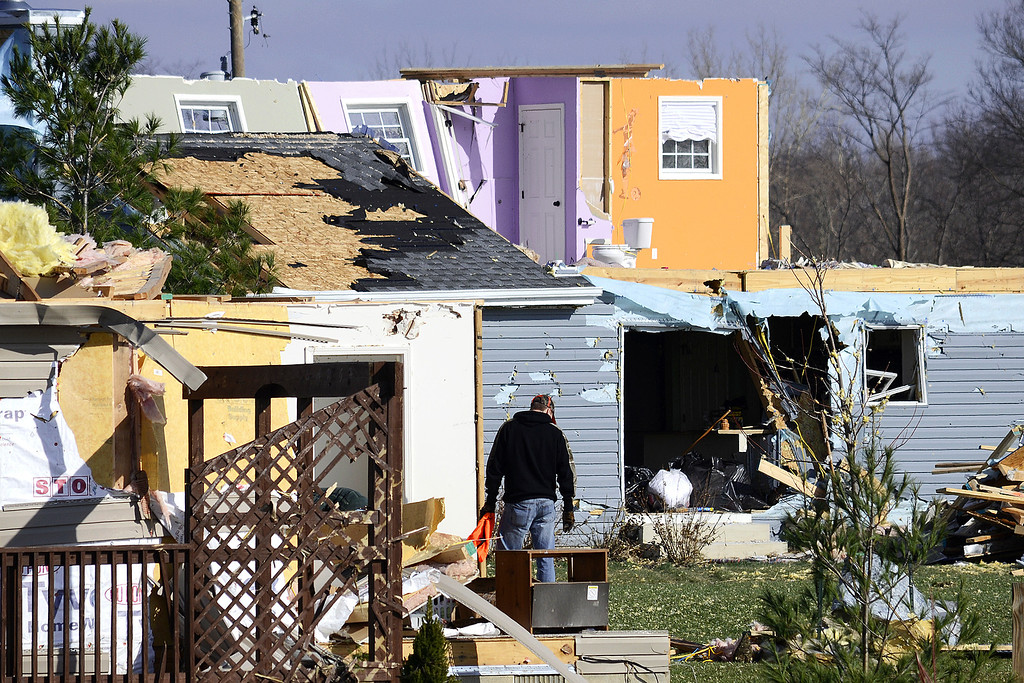 Description of . Residents comb through the wreckage of their storm-damaged homes on Tuesday, Nov. 19, 2013, south of Jalapa, Ind. The National Weather Service said Tuesday that at least 26 tornadoes touched down Sunday in Indiana, making it the second-biggest tornado outbreak in state history. Meteorologist John Kwiatkowski said the state's most active tornado day was June 2, 1990, when 33 tornadoes touched down.  (AP Photo/The Chronicle-Tribune, Jeff Morehead)