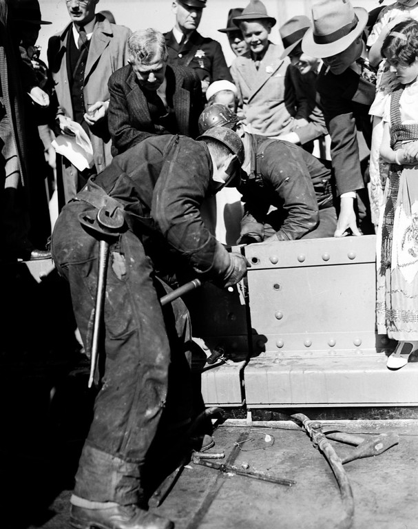 Description of . Ed Stanley drives the golden rivet to mark the completion of the $35,000,000 Golden Gate Bridge spanning the entrance to San Francisco Bay, Ca., April 29, 1937.  Holding the rivet is Ed Murphy and leaning over them is Joseph B. Strauss, chief engineer of the project.  The bridge will be opened to the public May 27.  (AP Photo)