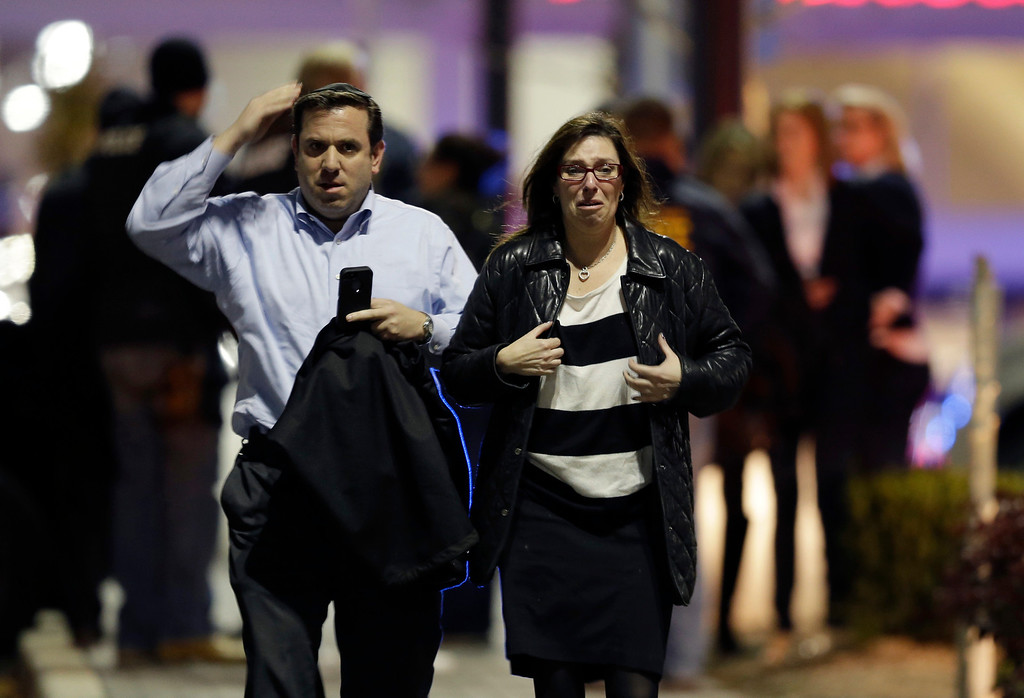 Description of . A man and woman leave the Garden State Plaza Mall with officials standing guard behind them following reports of a shooter, Monday, Nov. 4, 2013, in Paramus, N.J. Hundreds of law enforcement officers converged on the mall Monday night after witnesses said multiple shots were fired there. (AP Photo/Julio Cortez)