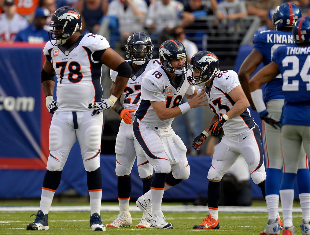 Description of . Broncos Quarterback Peyton Manning (18)  gives some instructions to wide receiver Wes Welker (83) of the Denver Broncos during the first quarter against the New York Giants September 15, 2013 MetLIFE Stadium. (Photo by John Leyba/The Denver Post)