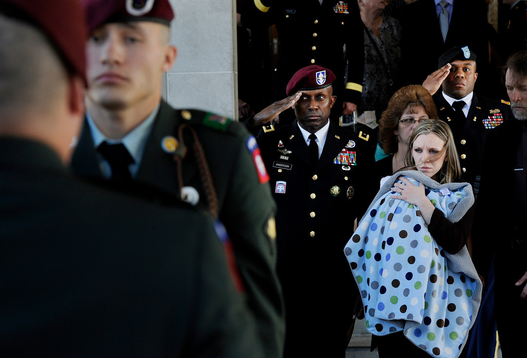 Description of . Sarah Bear holds her son, Kayden, following the funeral service for her husband,U.S. Army Staff Sgt. Jordan L. Bear at All Saints Roman Catholic Church in Denver, CO, Tuesday, March 13, 2012. Bear was killed in an attack on his base in Afghanistan. He was assigned to the 508th Parachute Infantry Regiment, 4th Brigade Combat Team, 82nd Airborne Division, at Fort Bragg, N.C. Bear was a member of the Ponca Indian tribe. He was buried at Fort Logan National Cemetery. Craig F. Walker, The Denver Post