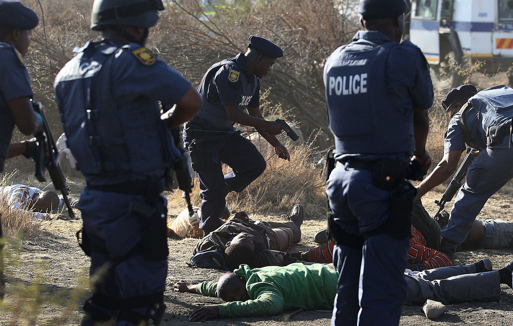 Description of . In this Aug. 16, 2012 file photo, police surround the bodies of striking miners after opening fire on a crowd at the Lonmin Platinum Mine near Rustenburg, South Africa. South African police opened fire on a crowd of striking workers at a platinum mine, leaving an unknown number of people injured and possibly dead. Motionless bodies lay on the ground in pools of blood.  (AP Photo/File)