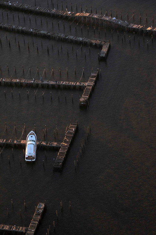Description of . A boat sits on top of a pier in this aerial view near Atlantic Highlands, New Jersey, almost a month after the area was hit by Hurricane Sandy, November 28, 2012.   REUTERS/Adrees Latif