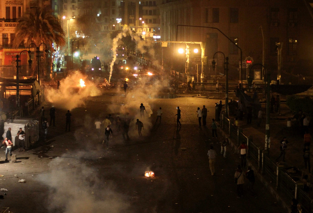 Description of . Tear gas fills downtown as protesters clash with security forces in downtown Cairo, Egypt, Saturday, April 6, 2013. Police fired tear gas at hundreds of protesters outside the chief prosecutor's office Saturday in central Cairo who were pushing on the building's doors demanding he resign.(AP Photo/Mostafa Elshemy)