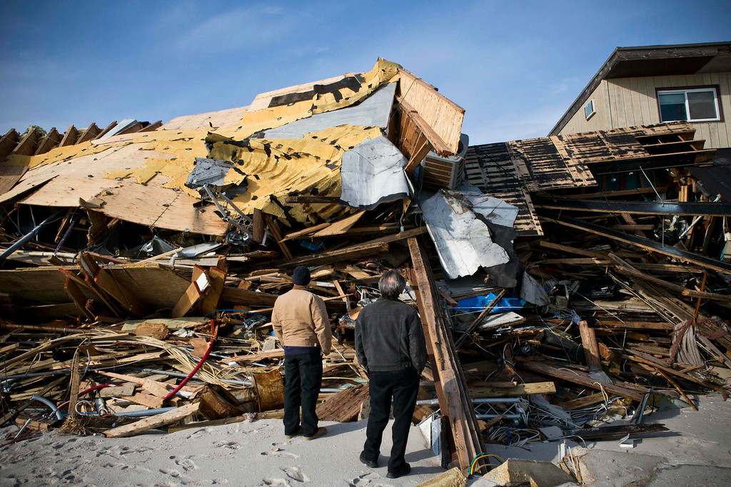 Description of . Men survey the damage caused by Hurricane Sandy in the Ortley Beach area of Toms River, New Jersey November 28, 2012. The storm made landfall along the New Jersey coastline on October 29. REUTERS/Andrew Burton