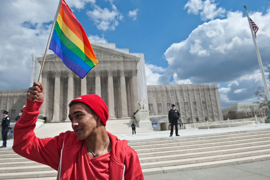 Description of . A young man holds a rainbow flag in front of the US Supreme Court in Washington on March 26, 2013 as the court hears arguments on California\'s Proposition 8 ban on same-sex marriage.    AFP PHOTO/Nicholas  KAMM/AFP/Getty Images