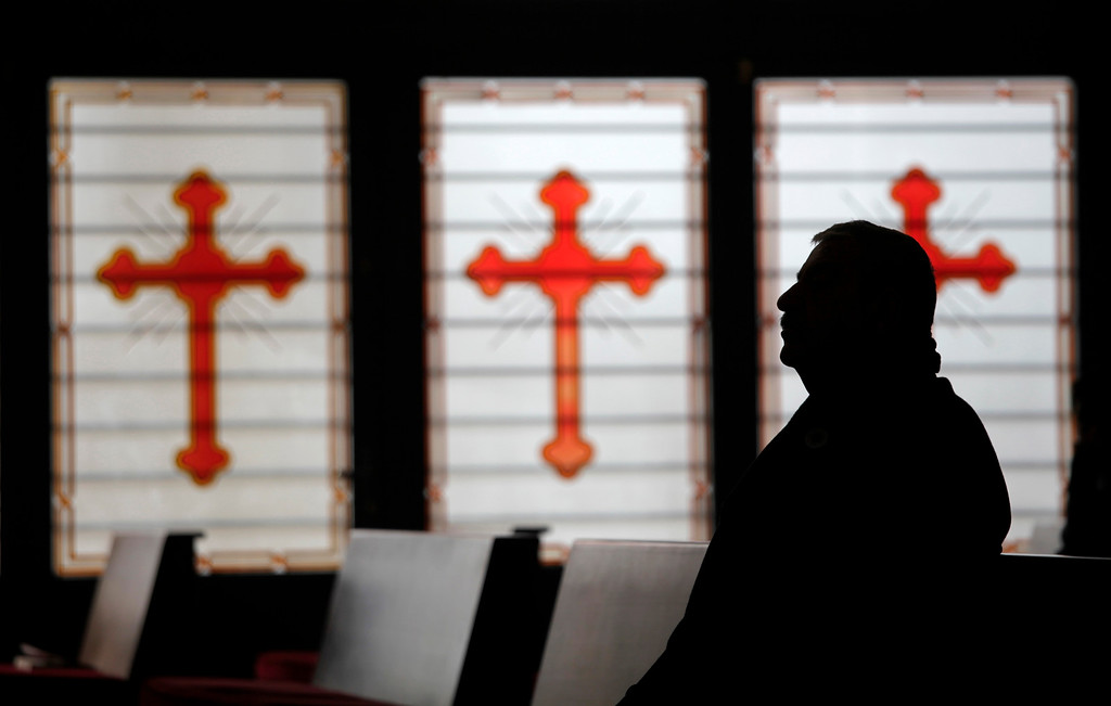 Description of . An Iraqi Orthodox Christian refugee attends a morning Christmas mass at the Saint Afram Syrian Orthodox Church in Amman, Jordan, Wednesday, Dec. 25, 2013. Syrian and Iraqi Orthodox Christian families attended morning mass of Christmas and pray for peace in their countries. (AP Photo/Mohammad Hannon)