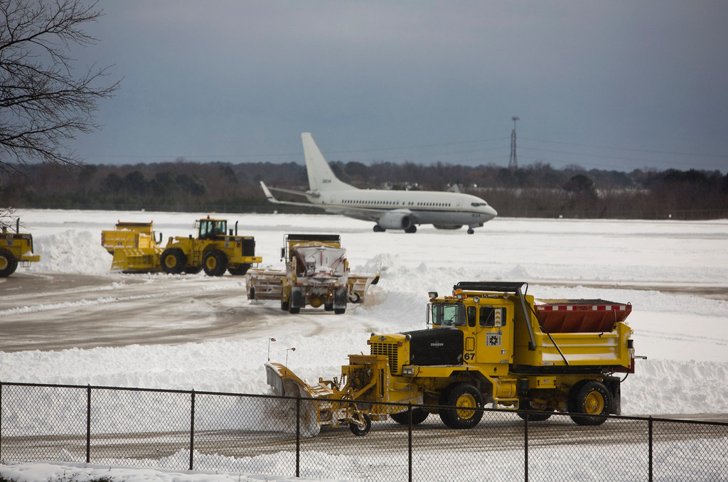 Description of . Crews plow the tarmac at Norfolk International Airport in Norfolk, Va. Wednesday, Jan. 29, 2014.  Most flights in and out of the airport were delayed or canceled. The coast of Virginia was blanketed in up to 10 inches of snow Wednesday, with many workers in the heavily populated Hampton Roads region being told to stay home rather than travel to work in dangerous conditions. (AP Photo/The Virginian-Pilot, The' N. Pham)