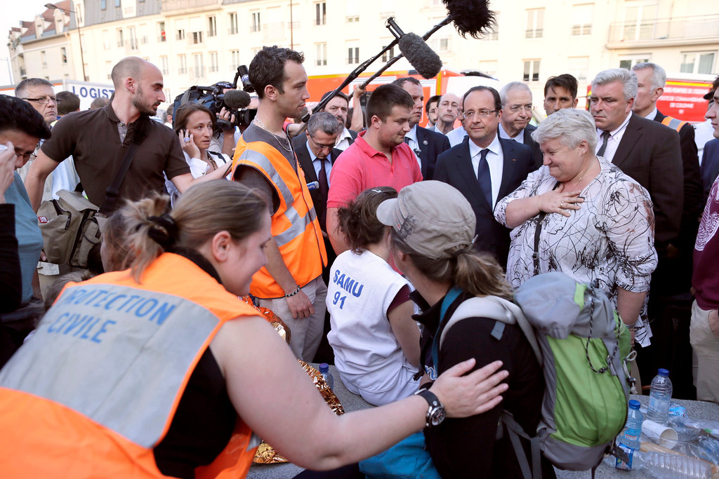 Description of . French President Francois Hollande (3rdR) is surrounded by victims and rescue workers during a visit on the site of an intercity train accident at the Bretigny-sur-Orge train station near Paris July 12, 2013. REUTERS/Kenzo Tribouillard/Pool