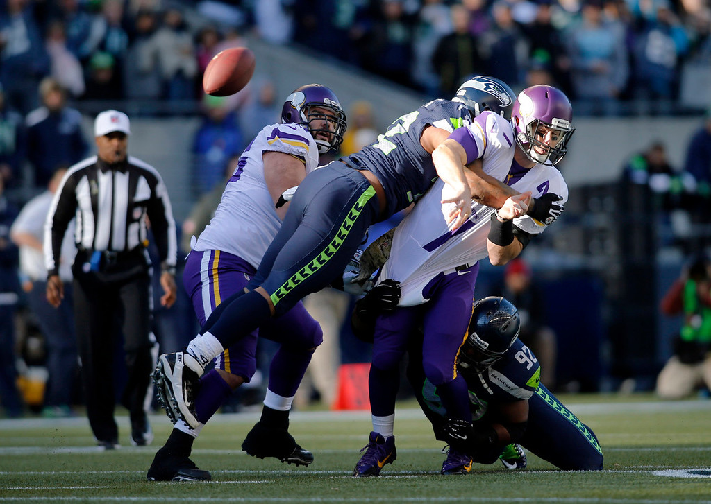 Description of . Minnesota Vikings quarterback Christian Ponder, right, is hit by Seattle Seahawks' Michael Bennett, second from left, and Brandon Mebane (92), right, as he attempts a pass in the first half of an NFL football game Sunday, Nov. 17, 2013, in Seattle. The Seahawks won 41-20. (AP Photo/John Froschauer)