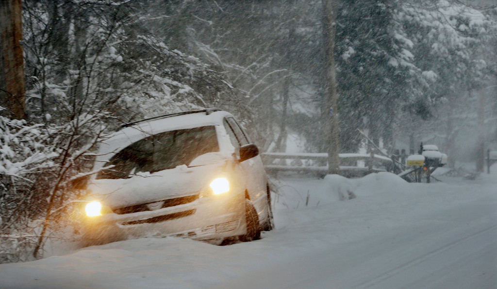 Description of . A car is stuck in the snow after skidding into a ditch in Yardley, Pa., Thursday, Feb. 13, 2014. A winter storm dumped more than a foot of snow in parts of the Mid-Atlantic region as it marched Northeast and threatened more power outages, traffic headaches and widespread closures for millions of residents.  (AP Photo/Mel Evans)