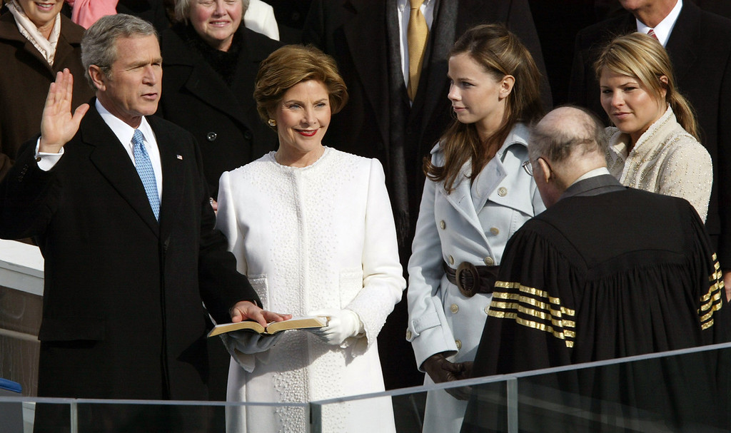 Description of . President Bush takes the oath of office from Chief Justice William Rehnquist, right, with first lady Laura Bush, and his daughters Barbara and Jenna at his side at the US Capitol in Washington, Jan. 20, 2005. In background are Speaker of the House Dennis Hastert, left, and Sen. Trent Lott, R-Miss. (AP Photo/Paul Sancya)