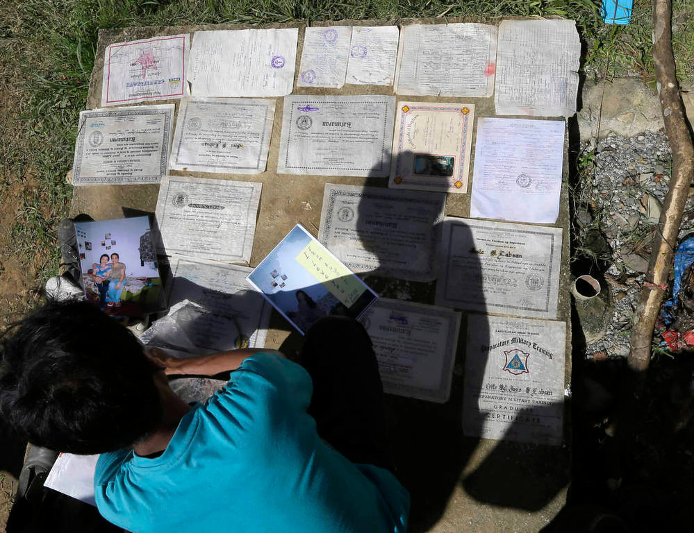 Description of . Typhoon evacuees dry documents and family photos at an evacuation center at Maparat township, Compostela Valley in southern Philippines Saturday Dec. 8, 2012. Search and rescue operations following typhoon Bopha that killed nearly 600 people in the southern Philippines have been hampered in part because many residents of this ravaged farming community are too stunned to assist recovery efforts, an official said Saturday. (AP Photo/Bullit Marquez)