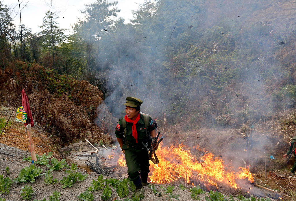 Description of . A soldier from Ta-ang National Liberation Army (TNLA), one of the ethnic rebel groups, walks out from a burning poppy field in Loi Mel Main village, Man Tone Township, Northern Shan State, Myanmar. Myanmar's opium production in 2013 was expected to reach 870 tons, a 26-per-cent increase year-on-year, for a 13-per-cent increase in cultivated area, the United Nations said. Last year, Myanmar produced an estimated 690 tons of opium, compared with 41 tons in Laos and 3 tons in Thailand, the three significant producers in South-East Asia. Myanmar was the world's largest source of opium and its derivative heroin in the early 1990s, but is now ranked second after Afghanistan. Myanmar's northern Shan State, home to several insurgencies including the Shan State Army and United Wa State Army, accounted for 92 per cent of opium poppy cultivation this year, with the remainder located in neighbouring Kachin State, where government troops and the Kachin Independence Army have been fighting since 2011, the report sai EPA/NYEIN CHAN NAING