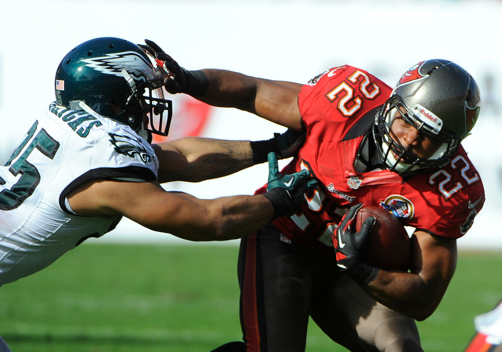 Description of . Tampa Bay Buccaneers running back Doug Martin (22) pushes off Philadelphia Eagles outside linebacker Mychal Kendricks (95) on a run during the second quarter of an NFL football game Sunday, Dec. 9, 2012, in Tampa, Fla. (AP Photo/Brian Blanco)