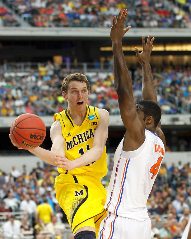 . Michigan Wolverines guard Nik Stauskas goes around Florida Gators center Patric Young (R) in their South Regional NCAA men\'s basketball game in Arlington, Texas March 31, 2013. REUTERS/Mike Stone