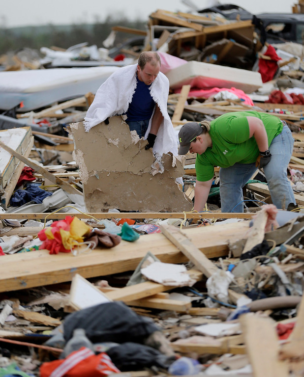 Description of . Mark Wade, left, and family friend Alicia Henson, right, search for personal items after his home was destroyed by Sunday's tornado, Tuesday, April 29, 2014, in Vilonia, Ark.  (AP Photo/Eric Gay)