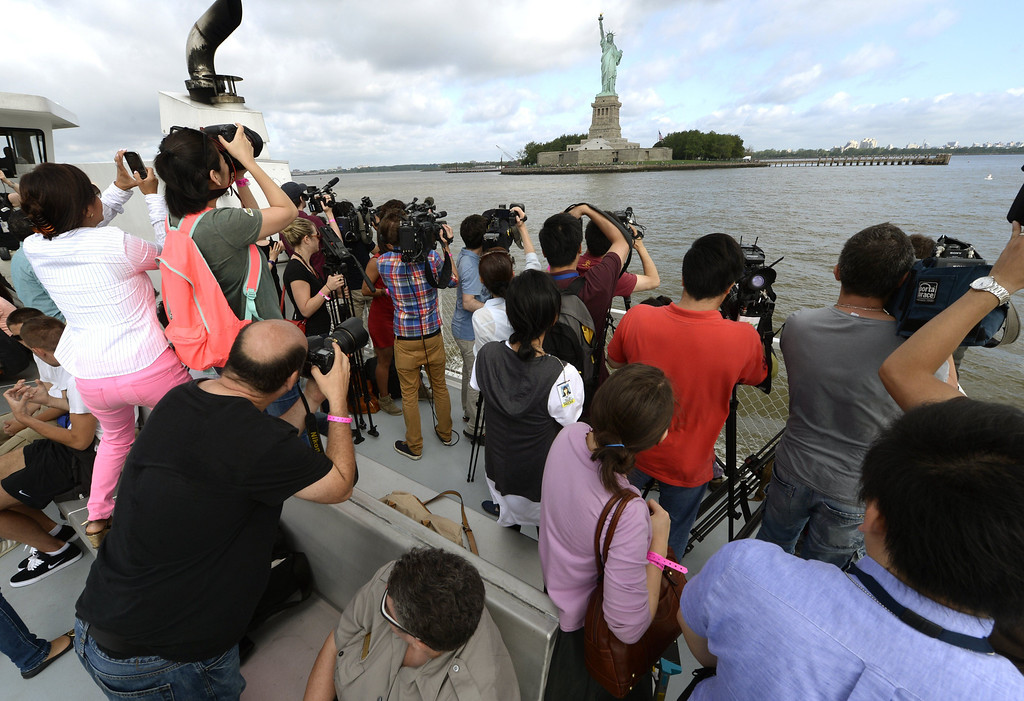 Description of . People take photos of the Statue of Liberty, as Liberty Island opens to the public on July 4, 2013 for the first time since Superstorm Sandy slammed into the New York area. The Statue of Liberty, one of America's most recognizable symbols, reopens just in time for the July 4 national holiday, after being repaired from damage inflicted last year by Hurricane Sandy. TIMOTHY CLARY/AFP/Getty Images