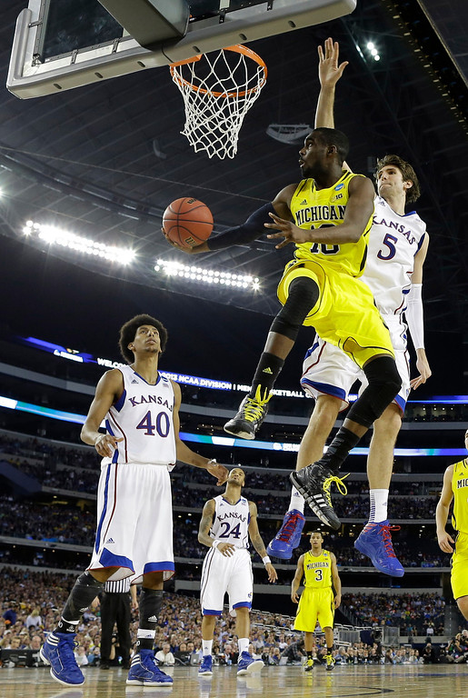 Description of . Michigan\'s Tim Hardaway Jr. (10) drives past Kansas\' Jeff Withey (5) during the second half of a regional semifinal game in the NCAA college basketball tournament, Friday, March 29, 2013, in Arlington, Texas. (AP Photo/David J. Phillip)