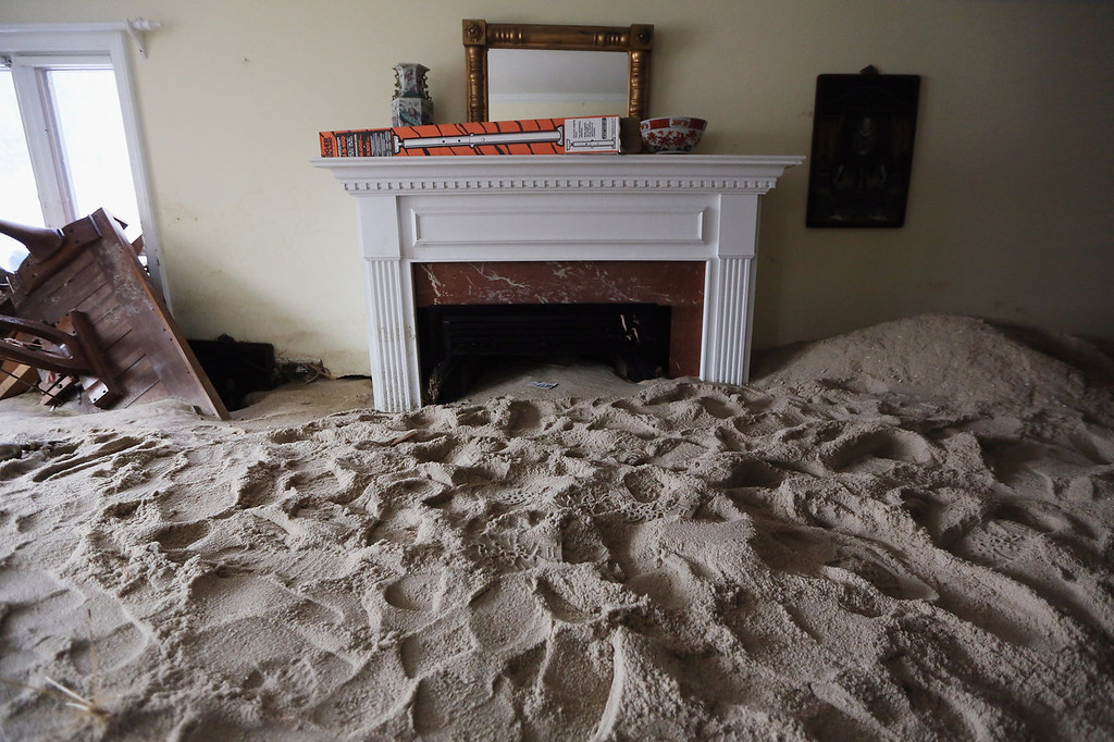 . A living room is filled with sand washed in by Superstorm Sandy on November 14, 2012 in Point Pleasant Beach, New Jersey. Many residents of the hard hit seaside town remain without power following Superstorm Sandy. (Photo by Mario Tama/Getty Images)