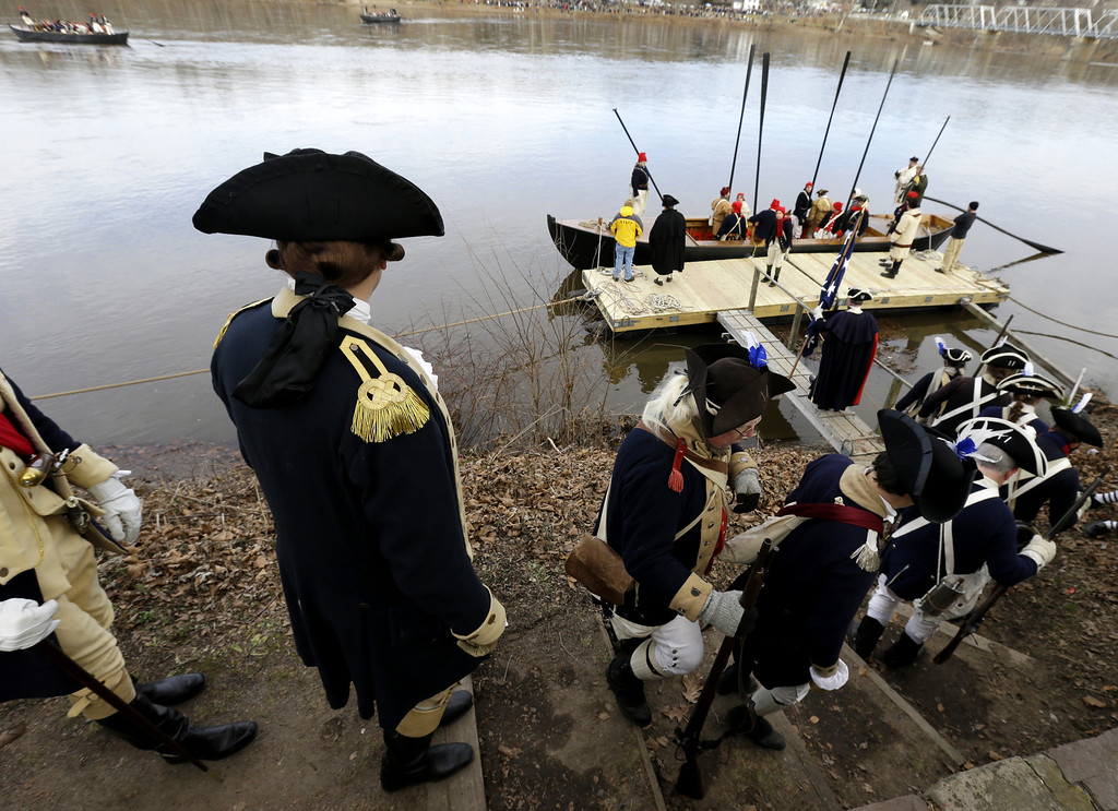 Description of . John Godzieba, left, playing the role of Gen. George Washington, walks behind his troops onto a dock during the 61st annual re-enactment of Washington's daring Christmas 1776 crossing of the river, the trek that turned the tide of the Revolutionary War, in Washington Crossing, N.J. During the crossing 237 years ago, boats ferried 2,400 soldiers, 200 horses and 18 cannons across the river, and the troops marched eight miles downriver before battling Hessian mercenaries in the streets of Trenton. (AP Photo/Julio Cortez)