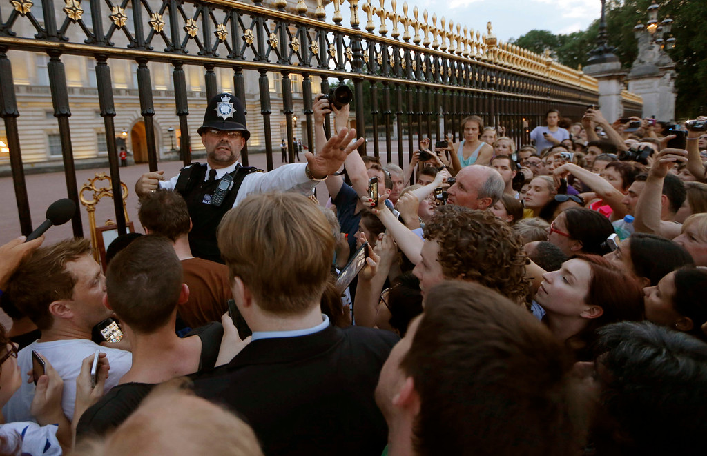 Description of . A police officer tries to control a crowd of people trying to get to the railing to take pictures of a notice proclaiming the birth of a baby boy to Prince William and Kate, Duchess of Cambridge on display for  public view at Buckingham Palace in London, Monday, July 22, 2013. (AP Photo/Sang Tan)