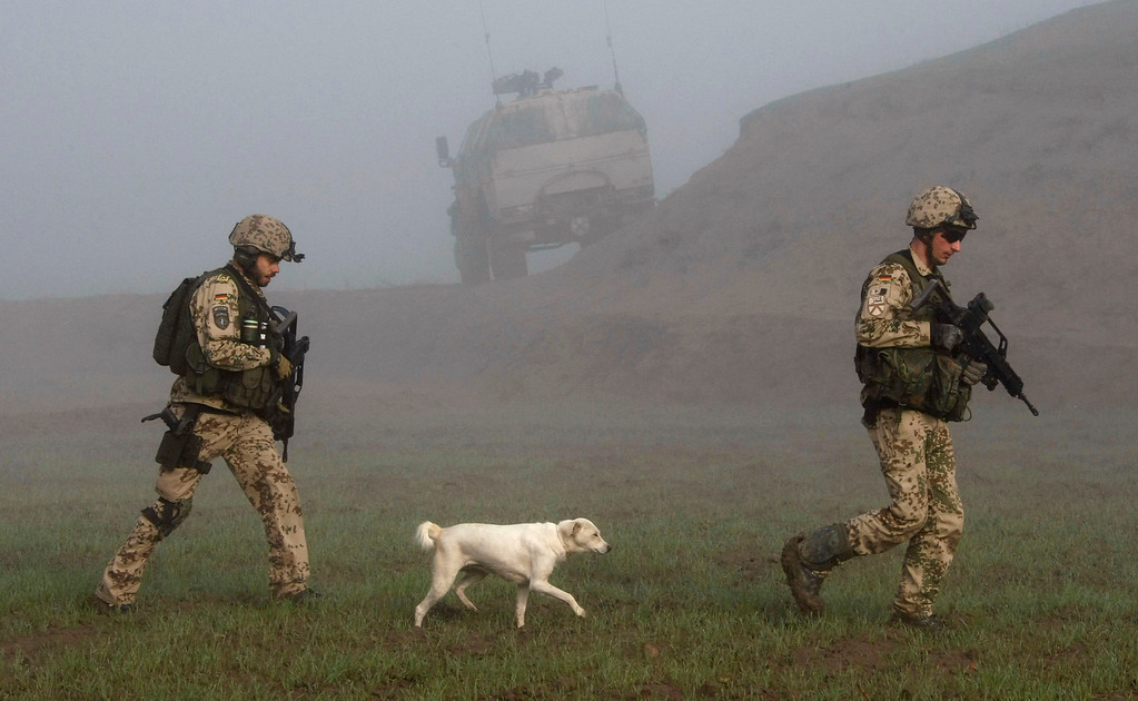 . A dog follows German Bundeswehr army soldiers of the International Security Assistance Force (ISAF) during a mission in Chahar Dara in the outskirts of Kunduz, December 17, 2009. German Bundeswehr army soldiers and Afghan National Army (ANA) units started a operation against insurgents in the area on Wednesday. REUTERS/Fabrizio Bensch