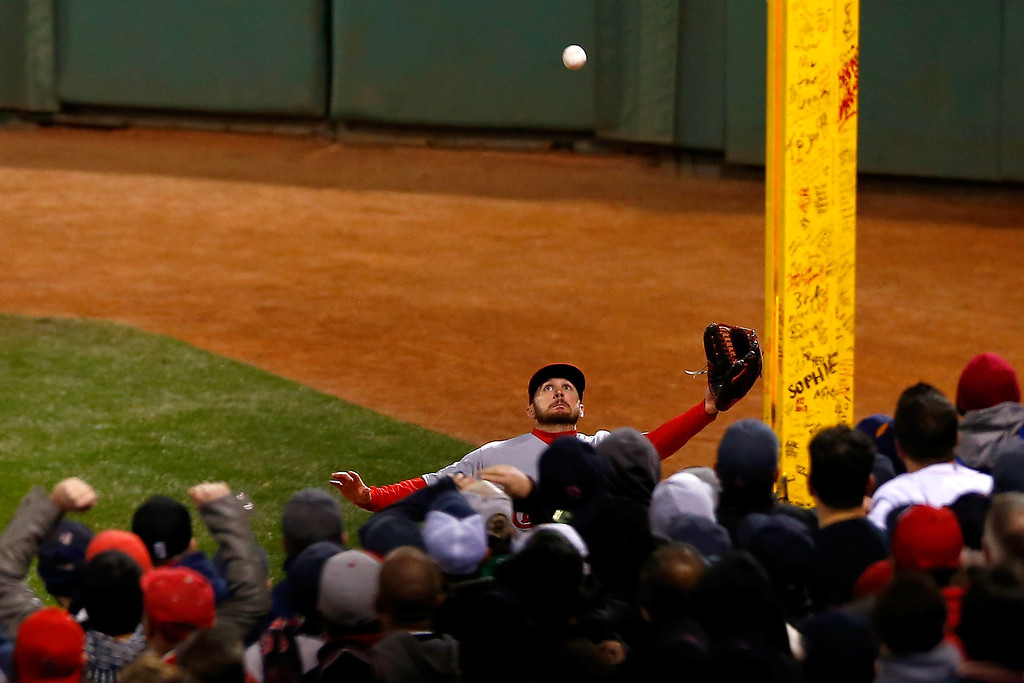 Description of . Shane Robinson #43 of the St. Louis Cardinals makes a catch against the Boston Red Sox in the fifth inning of Game One of the 2013 World Series at Fenway Park on October 23, 2013 in Boston, Massachusetts.  (Photo by Jared Wickerham/Getty Images)