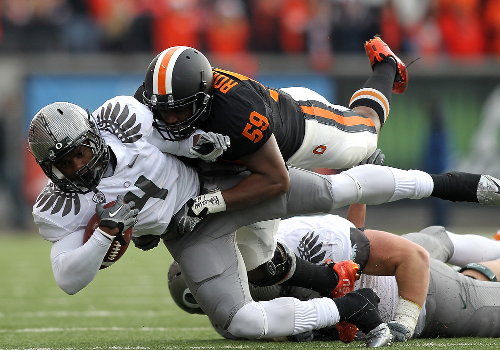 Description of . Josh Huff #4 of the Oregon Ducks runs te ball against Dwight Roberson #59 of the Oregon State Beavers during the 114th Civil War on December 4, 2010 at the Reser Stadium in Corvallis, Oregon.  (Photo by Jonathan Ferrey/Getty Images)