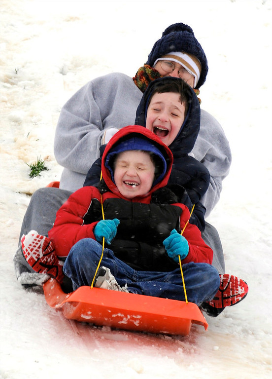Description of . While blizzard conditions made travel difficult, (front to back) John Michael Randolph, 6 years-old, Brecken Randolph, 9 years-old, and Kristie Randolph took advantage of the snow to go sledding at Atkinson Park in Henderson, Ky., Wednesday, Dec. 26, 2012. (AP Photo/The Gleaner, Mike Lawrence)