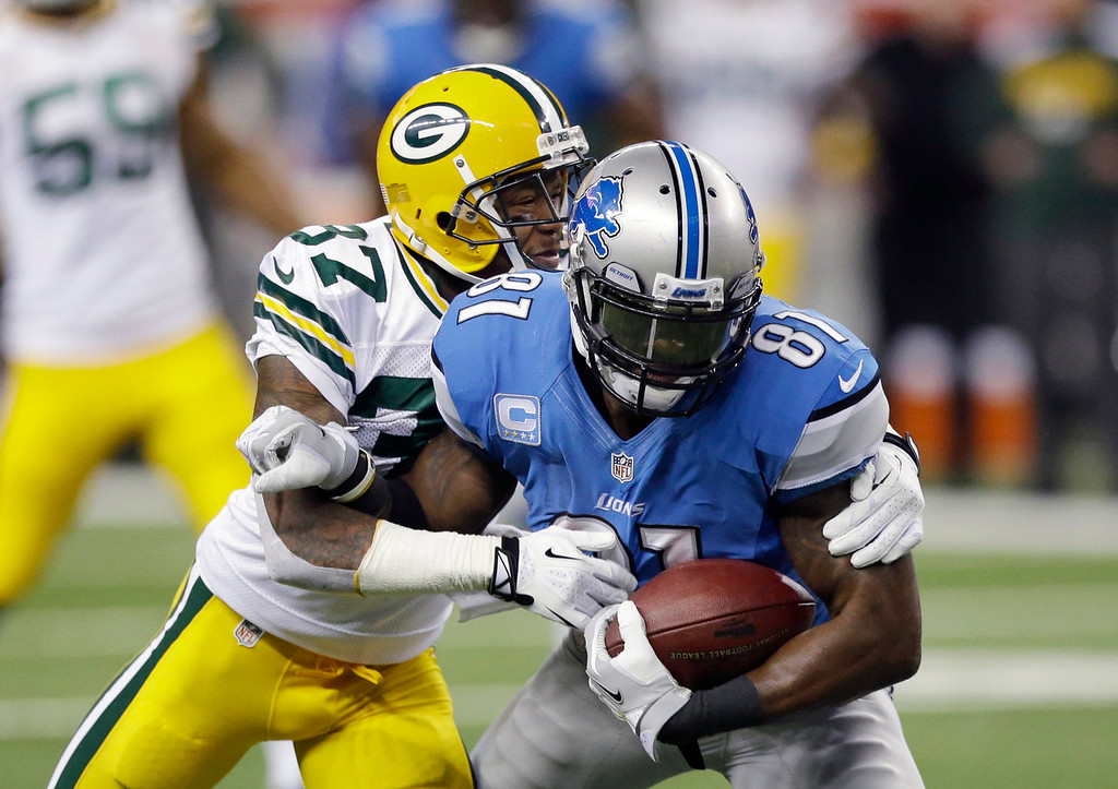 . Detroit Lions wide receiver Calvin Johnson (81) is stopped by Green Bay Packers cornerback Sam Shields (37) during the first quarter of an NFL football game at Ford Field in Detroit, Thursday, Nov. 28, 2013. (AP Photo/Carlos Osorio)