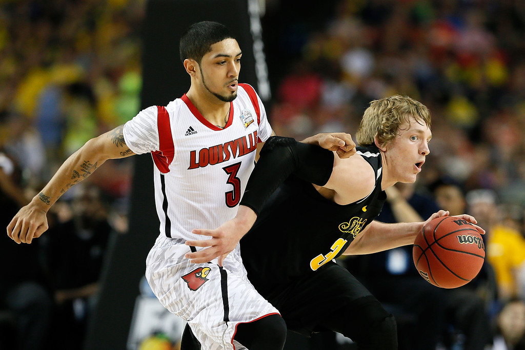 Description of . ATLANTA, GA - APRIL 06:  Ron Baker #31 of the Wichita State Shockers moves the ball against Peyton Siva #3 of the Louisville Cardinals in the first half during the 2013 NCAA Men's Final Four Semifinal at the Georgia Dome on April 6, 2013 in Atlanta, Georgia.  (Photo by Kevin C. Cox/Getty Images)