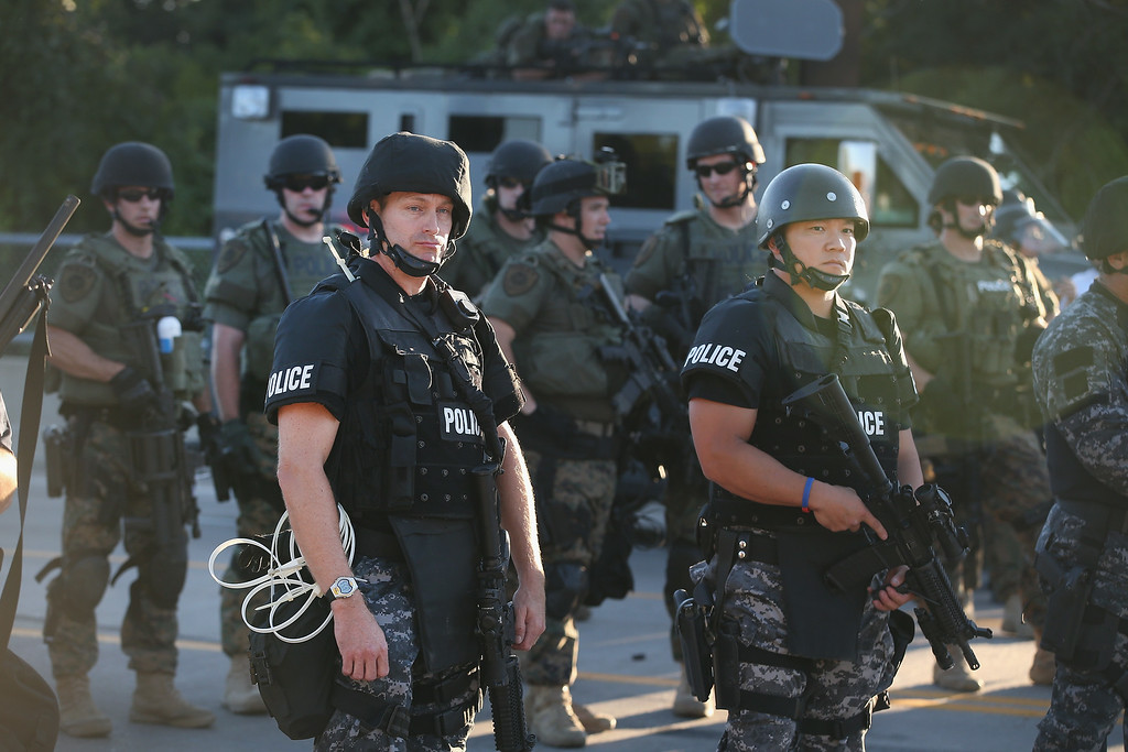 Description of . FERGUSON, MO - AUGUST 12:  Police take up position to control demonstrators who were protesting the killing of teenager Michael Brown on August 12, 2014 in Ferguson, Missouri. Brown was shot and killed by a police officer on Saturday in the St. Louis suburb of Ferguson. Ferguson has experienced two days of violent protests since the killing but, tonight\'s protest was peaceful.  (Photo by Scott Olson/Getty Images)