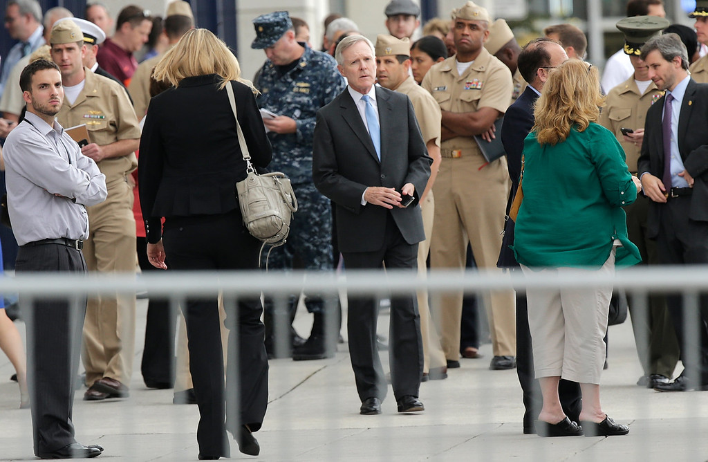 Description of . Secretary of the Navy Ray Mabus (C) visits a gathering point for reuniting family members of Navy Yard employees that was set up inside Nationals Park in the wake of the shooting September 16, 2013 in Washington, DC. Police believe at least one gunman shot and killed at least 12 people and wounded others in an incident that put parts of the city on lockdown. (Photo by Win McNamee/Getty Images)