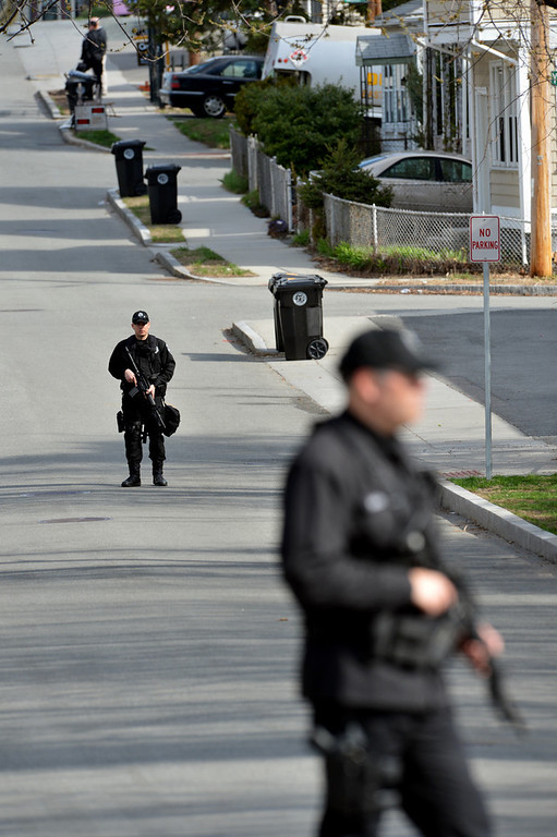 Description of . Police monitor a locked down street as a search for the second of two suspects wanted in the Boston Marathon bombings takes place on April 19, 2013 in Watertown, Massachusetts. Dzhokhar and Tamerlan Tsarnaev, suspected of bombing the Boston marathon, appear to hail from Russia's war-torn Chechnya but had been in the United States for several years. Tamerlan reportedly died in a shootout with police on April 19 and his yournger brother fled and is being sought by police.  STAN HONDA/AFP/Getty Images
