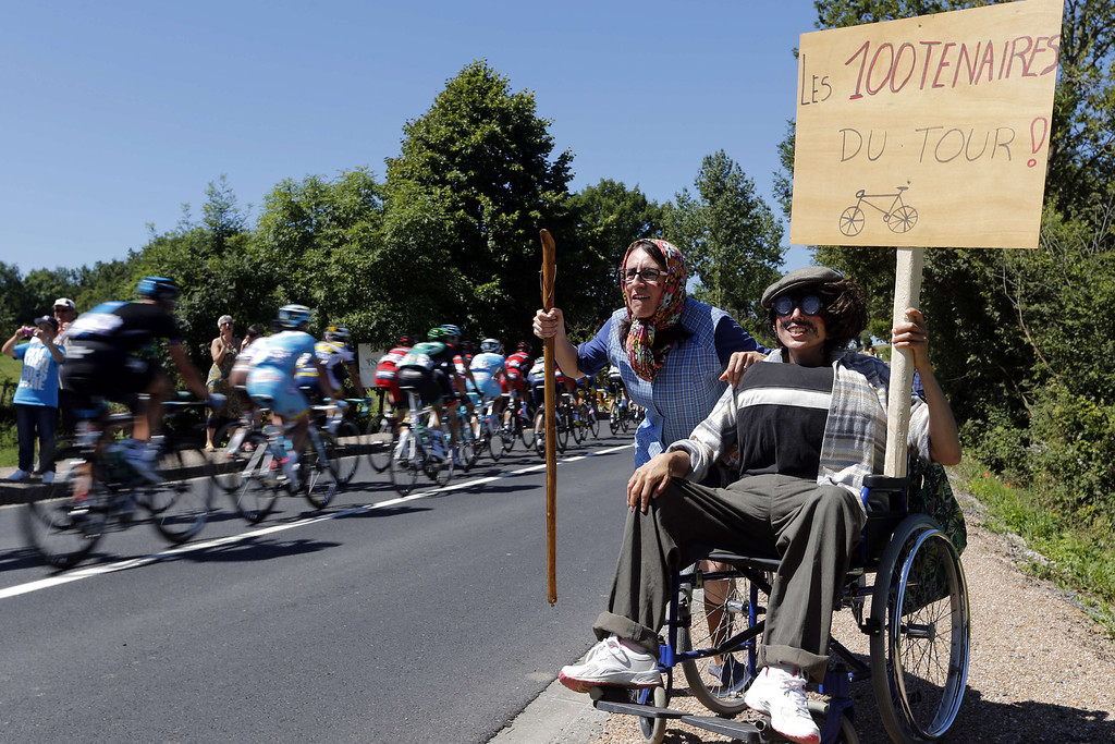 ". Spectators disguised as elderly persons cheer riders as they hold a placard reading ""The centenarian people of the Tour !\"" in reference of the centenary of the Tour de France cycling race, during the 195 km eighth stage of the 100th edition of the Tour de France cycling race on July 6, 2013 between Castres and Ax 3 Domaines, southwestern France. JOEL SAGET/AFP/Getty Images"