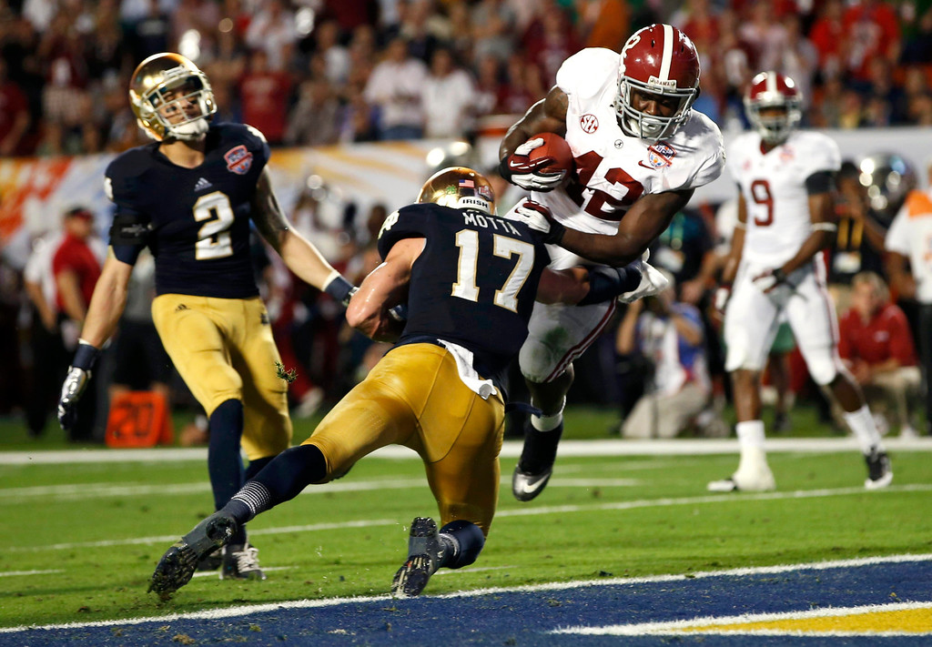 Description of . Alabama Crimson Tide running back Eddie Lacy (42) scores a touchdown past Notre Dame Fighting Irish safety Zeke Motta and cornerback Bennett Jackson (2) during the second quarter of their NCAA BCS National Championship college football game in Miami, Florida, January 7, 2013. REUTERS/Mike Segar