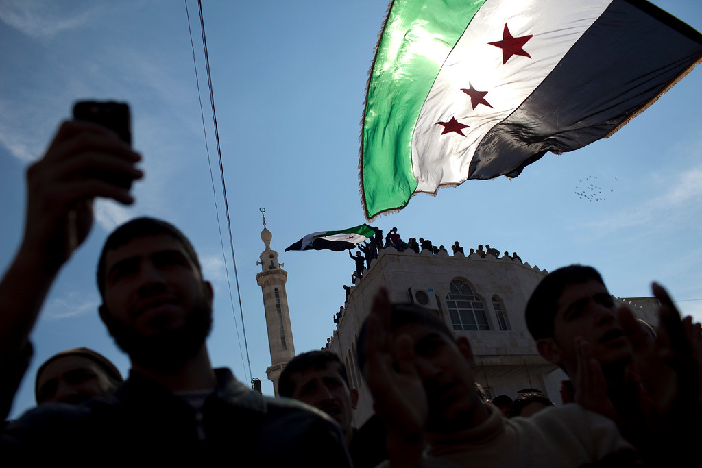 Description of . In this Friday, March 2, 2012 file photo, men hold revolutionary Syrian flags during an anti government protest in a town in north Syria. More than two years into Syria's civil war, the once highly-centralized authoritarian state has effectively split into three distinct parts, each boasting its own flags, security agencies and judicial system. (AP Photo/Rodrigo Abd)