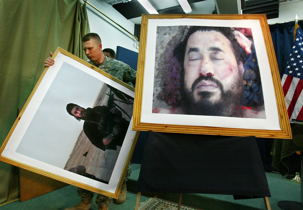 Description of . A U.S. soldier at a press conference in Baghdad, Iraq, takes down an older image, to display the latest image purporting to show the body of Abu Musab al-Zarqawi, the al-Qaida-linked militant who led a bloody campaign of suicide bombings, kidnappings and hostage beheadings in Iraq, who was killed Wednesday in a U.S. airstrike, Iraq's Prime Minister Nouri al-Maliki announced, in this June 8, 2006, file photo. (AP Photo/Khalid Mohammed/FILE)