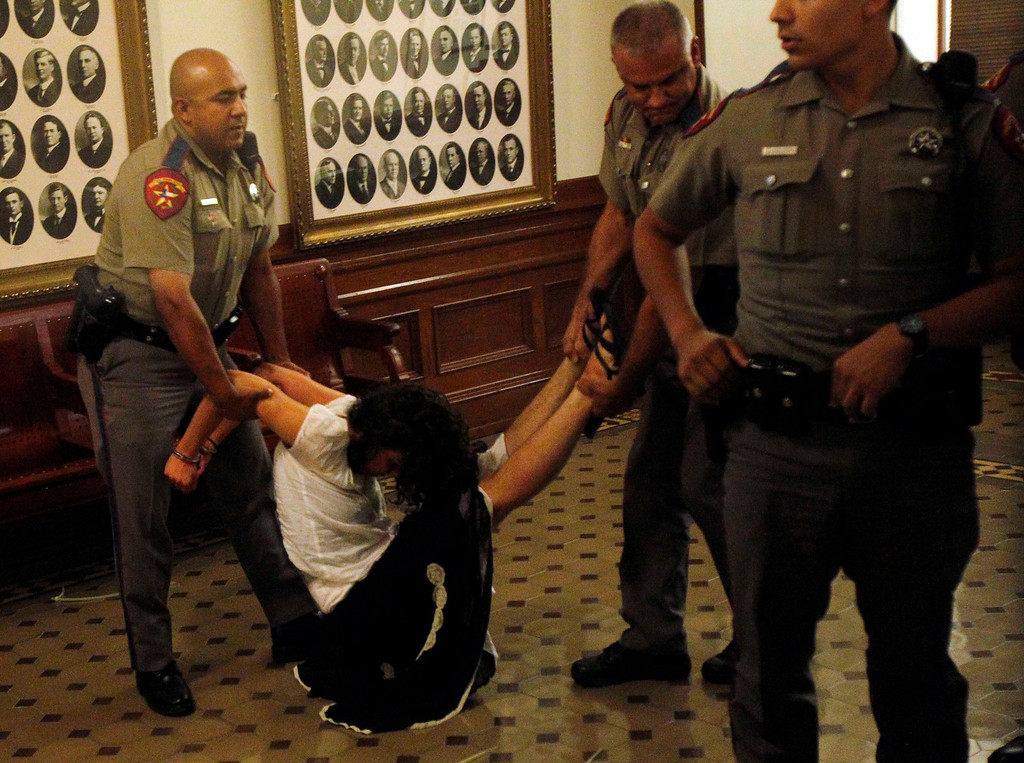 Description of . An abortion rights activist is handcuffed after being removed from the Senate gallery after disrupting the Senate's special session to consider legislation restricting abortion rights in Austin, Texas July 12, 2013. The Republican proposal that would ban most abortions in Texas after 20 weeks of pregnancy moved toward a possible final vote in the state Senate Friday, and Democrats fiercely opposed to the measure conceded they will not be able to stop it. Davis drew national attention last month by staging a filibuster on the final day of a special session.  REUTERS/Mike Stone