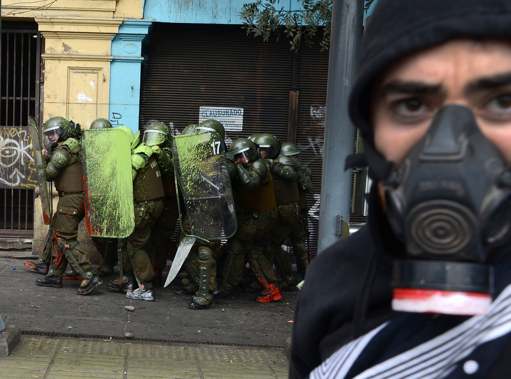 Description of . Students clash with riot police during a protest to demand Chilean President Sebastian Pinera\'s government to improve the public education quality, in Santiago, on April 11,2013. PABLO TAPIA/AFP/Getty Images