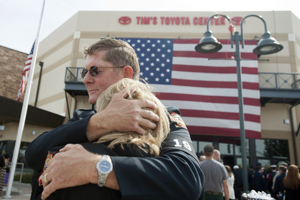 Description of . Chaplain Bob Ossler with the Mayer, Arizona fire department hugs Mary Dalton, assistant chief of the Sun City West Fire Department, at the entrance to a memorial service honoring the 19 firefighters killed in a wildfire at Tim's Toyota Center July 9, 2013 in Prescott Valley, Arizona. (Photo by Laura Segall/Getty Images)