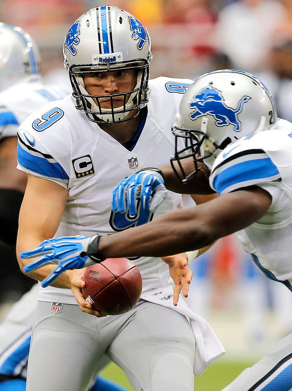 Description of . Detroit Lions quarterback Matthew Stafford (9) fakes a handoff to teammate Reggie Bush during the first half of a NFL football game against the Arizona Cardinals, Sunday, Sept. 15, 2013, in Glendale, Ariz. (AP Photo/Matt York)
