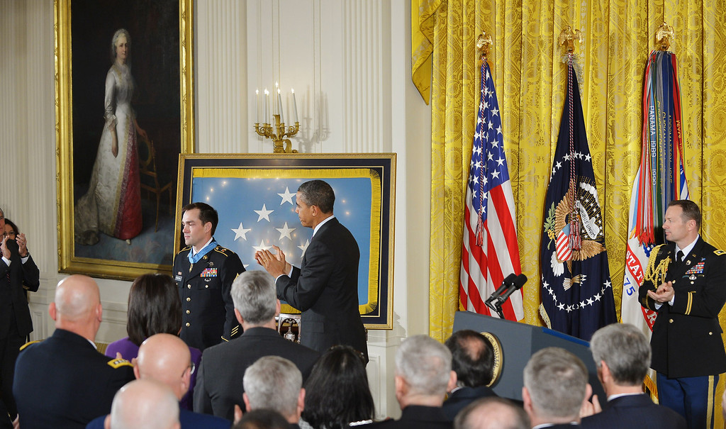Description of . US President Barack Obama applauds after presenting Clinton Romesha, former active duty Army staff sergeant, with the Medal of Honor during a ceremony in the East Room of the White House on February 11, 2013 in Washington, DC.  AFP PHOTO/Mandel NGAN/AFP/Getty Images